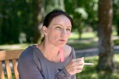 Dojrzały kobiety dymienia papieros na ławce w parku fotografia stock