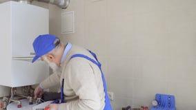 Dojrzały mężczyzna jest ubranym błękitnych kombinezony egzamininuje łamanie drymby od bojleru zbiory wideo