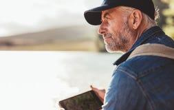Dojrzały mężczyzna jest ubranym nakrętki obsiadanie przy jeziorem i patrzeje widok Obrazy Stock