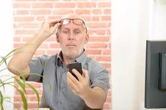 Dojrzały mężczyzna ma kłopot widzii telefonu ekran obrazy stock