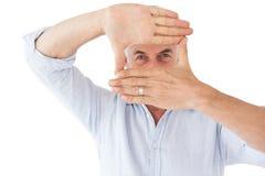 Dojrzały mężczyzna robi ramie z jego rękom zdjęcia stock