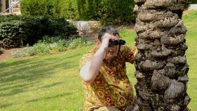 Dojrzały mężczyzna w koszula spojrzeniach przez lornetek aloha zamykał palmowy bagażnik w parku zdjęcie wideo