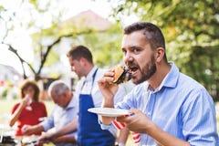 Dojrzały mężczyzna z rodziną i przyjaciółmi gotuje jedzenie na grilla przyjęciu fotografia royalty free