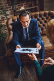 Dojrzały męski cierpliwy bierze papier z wizerunkiem Obraz Royalty Free