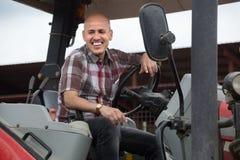 Dojrzały męski kierowca pracuje przy rolniczą maszynerią w gospodarstwie rolnym Obraz Stock
