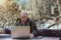 Dojrzały męski myśliwy z pastylka laptopem i komputerem osobistym fotografia stock