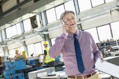 Dojrzały męski nadzorca opowiada na telefonie komórkowym w przemysle z schowkiem Fotografia Royalty Free