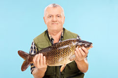 Dojrzały męski rybak trzyma słodkowodnej ryba Zdjęcie Royalty Free