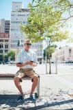 Dojrzały męski turystyczny odpoczywać na miasto ławce Zdjęcie Stock