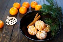 Dojrzały mandarine z liśćmi, tangerine mandarine pomarańcze w czarnym pucharze na drewnianym stołowym tle Cytrus owoc mandaryny w zdjęcie royalty free