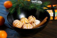 Dojrzały mandarine z liśćmi, tangerine mandarine pomarańcze w czarnym pucharze na drewnianym stołowym tle Cytrus owoc mandaryny w obraz stock