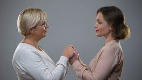 Dojrzały matki i dorosłego córki mienie wręcza patrzeć each inny, bliskość zbiory