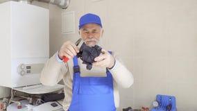Dojrzały mistrz egzamininuje plastikową część drymba i spojrzenia przy łamaniem na nim zdjęcie wideo