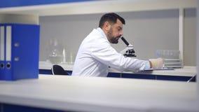 Dojrzały naukowiec patrzeje przez mikroskopu i zauważa obserwacje zbiory wideo