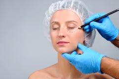 dojrzały ponad operacji plastycznej białą kobietą Doktorskie rysunkowe dziurkowanie linie na kobiety ` s stawiają czoło Zdjęcia Royalty Free