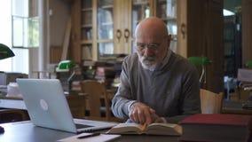 Dojrzały profesor pracuje z książką i laptopem siedzi przy stołem w bibliotece, zbiory