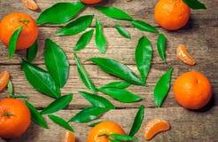 Dojrzały soczysty tangerine, pomarańczowa mandarynka z liśćmi na drewnianym knurze obrazy stock