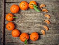 Dojrzały soczysty tangerine, pomarańczowa mandarynka z liśćmi na drewnianym knurze zdjęcie stock