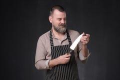 Dojrzały szef kuchni sprawdza ilość w fartucha kucharza mienia nożu zdjęcie royalty free