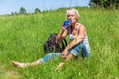 Dojrzała kobieta napojów woda przy wycieczkuje odpoczynkiem Obrazy Stock