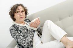 Dojrzała kobieta pije herbaty na kanapie Fotografia Stock