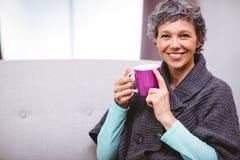 Dojrzała kobieta z kawowego kubka obsiadaniem na kanapie Fotografia Stock