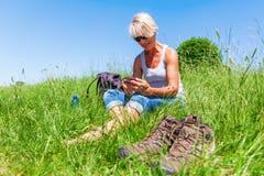 Dojrzała kobieta z telefonem przy wycieczkuje odpoczynkiem Fotografia Stock