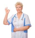 Dojrzała lekarka pokazuje ok gest Zdjęcia Royalty Free