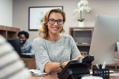 Dojrzała przypadkowa kobieta pracuje na komputerze obrazy royalty free