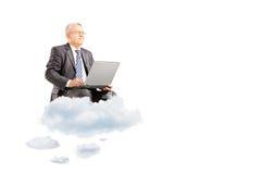 Dojrzały biznesmen jest ubranym kostium i latanie na chmurach z laptopem Obrazy Stock