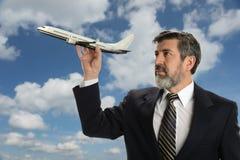 Dojrzały biznesmen trzyma samolot Fotografia Royalty Free