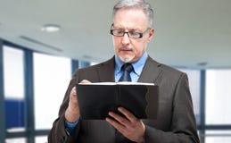 Dojrzały biznesmena writing na jego agendzie Fotografia Royalty Free