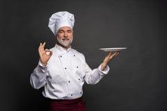 Dojrza?y kucbarski szef kuchni trzyma pustego talerza na czarnym tle zdjęcie royalty free