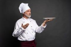 Dojrza?y kucbarski szef kuchni trzyma pustego talerza na czarnym tle obraz stock