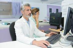 Dojrzały przystojny doktorski patrzeje egzamin wynika na komputerze Obrazy Royalty Free