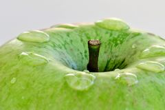 Dojrza?y zielony jab?ko na bia?ym tle z kroplami woda po deszczu zdjęcie stock