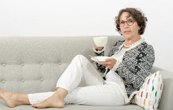 Dojrzała kobieta pije herbaty na kanapie Obraz Stock