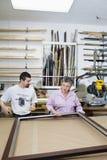 Dojrzałego pracownika obrazka pomiarowa rama z starszym właścicielem w warsztacie Obrazy Royalty Free