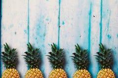 Dojrzali ananasy nad b??kitnym drewnianym sto?em zdjęcia stock