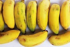 Dojrzali banany cią wpólnie w żółtym tle Zdjęcia Stock