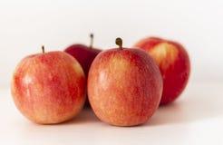 Dojrzali czerwoni jabłka na stole na białym tle obrazy royalty free