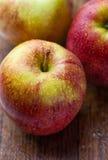 Dojrzali czerwoni jabłka na drewnianym tle Fotografia Stock