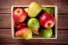 Dojrzali jabłka i bonkrety w drewnianym pudełku na ciemnego brązu drewnianym nieociosanym tle Jesień sezonowy wizerunek z odgórny fotografia royalty free
