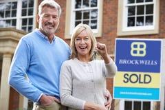 Dojrzali pary mienia klucze Nowa Domowa pozycja Sprzedającym znakiem obraz stock