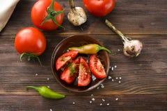 Dojrzali pokrojeni pomidory, gorącego chili pieprze, czosnek na drewnianym tabl Obrazy Stock