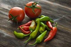 Dojrzali pomidory, gorącego chili pieprz na drewnianym stole Zdjęcia Royalty Free