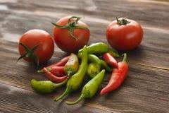 Dojrzali pomidory, gorącego chili pieprz na drewnianym stole Zdjęcia Stock