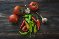 Dojrzali pomidory, gorącego chili pieprze, czosnek na drewnianym stole Obraz Royalty Free