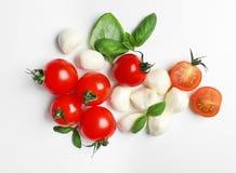 Dojrzali pomidory, mozzarella serowe piłki i basil na białym tle, odgórny widok Obraz Stock
