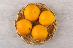 Dojrzali tangerines w łozinowym koszu na drewnianym stole Zdjęcie Stock